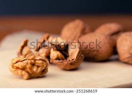 Close-up of Walnuts on a wooden board, one nut is cracked open. - stock photo