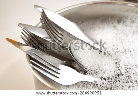 close up of washed dishes in the kitchen: silver spoons, forks and knifes.  - stock photo