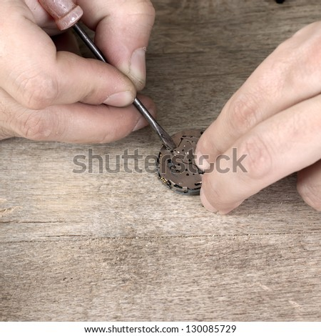 Close Up of watchmaker repairing battery in watches - stock photo