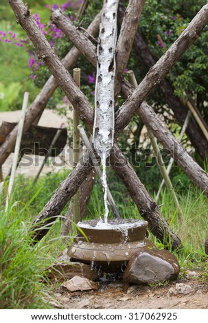 Close up of water flowing into a pot. Wastage of water concept. - stock photo