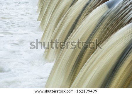 Close up of waterfall with brown silky water - stock photo