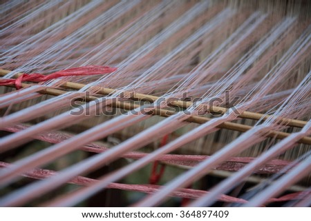 close up of weaving silk in traditional way at manual loom. Thailand - stock photo
