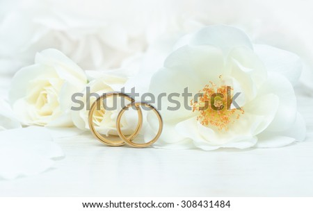 Close Up Of Wedding Rings On Background Roses