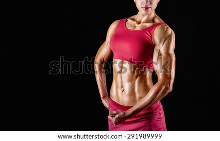 Close-up of wet body of a young athletic woman on a black background - stock photo