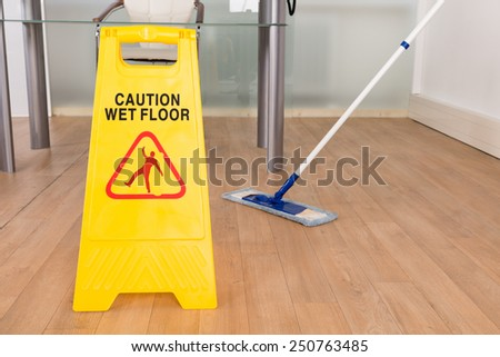 Close-up Of Wet Floor Sign And Mop On Hardwood Floor - stock photo