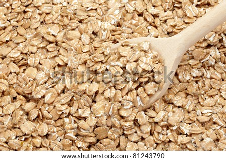 close up of wheat flakes in wooden spoon - stock photo