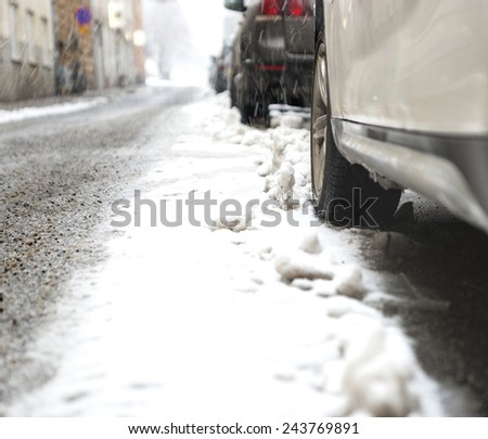 Close up of wheel of parked car in snow storm - stock photo