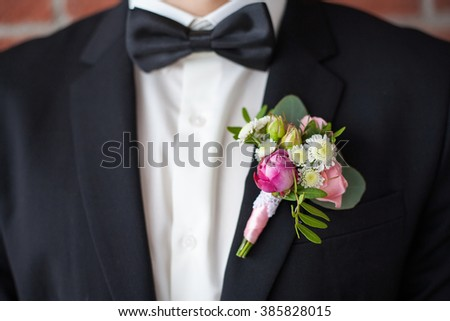 Close up of  white and pink rose corsage. Beautiful boutonniere pinned on man in black suit, white shirt and black bowtie. Groom or graduate. - stock photo