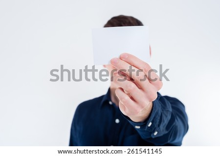 Close-up of white empty business card in business man hand - stock photo