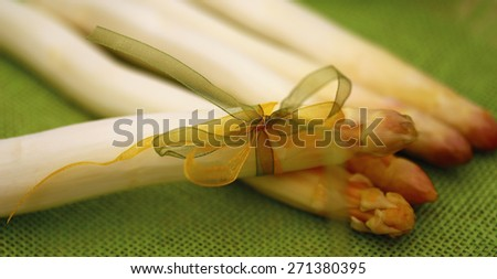 Close up of white fresh peeled asparagus with green and yellow bow on a green natural burlap fabric texture  background, shallow dof - stock photo