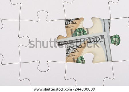 Close-up Of White Jigsaw Puzzle Over American Banknote - stock photo