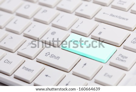 Close up of white keyboard with shallow depth of field and glowing blue enter button for concepts of technology the internet and communications
