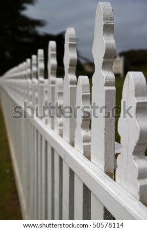 Close up of white picket fence diminishing to a soft focus - stock photo