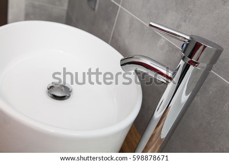 Close Up Of White Porcelain Sink With Chrome Faucet, Gray Tiles On The Wall,