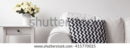 Close up of white room with sofa, pattern pillow, small table and bouquet of white flower in decorative pot - stock photo
