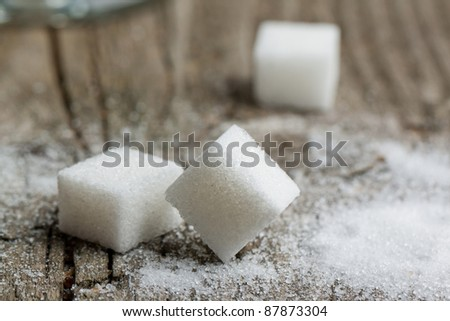 Close-up of white sugar on old wooden table - stock photo
