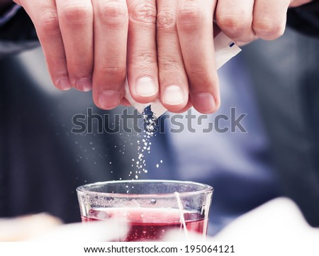 Close-up of white sugar particles falling in cup filled with tea. - stock photo