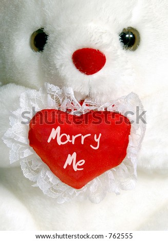 "Close up of white teddy bear with ""Marry Me"" heart"