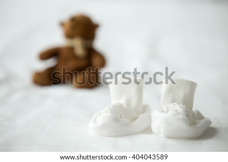 Close-up of white tiny booties for newborn baby on the bed. Cute teddy bear on the background. Maternity concept - stock photo