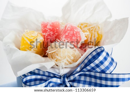 Close up of white yellow and pink coconut ice confectionery with fresh coconuts isolated on white