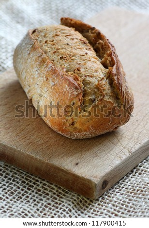 Close up of whole grain brown bread roll on top of chopping board