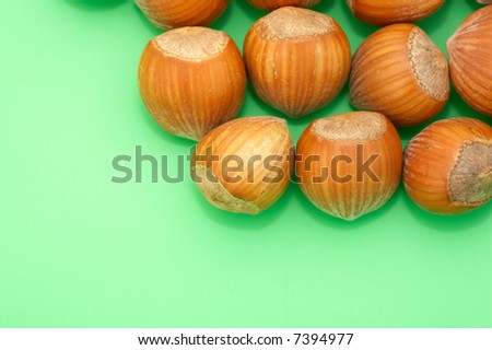 close-up of whole hazelnuts on green background - stock photo