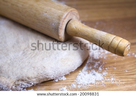 Close up of whole wheat dough being rolled out on a wooden table. - stock photo