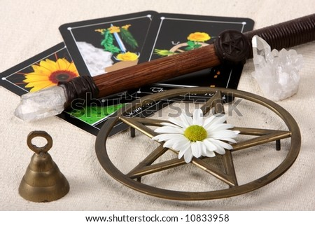 close up of wiccan objects - pentacle wand bell crystal and flowerwith tarot cards