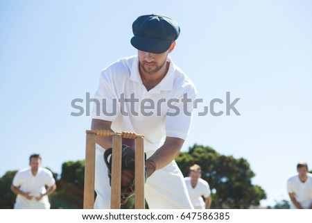 Close up of wicket keeper standing by stumps against clear sky