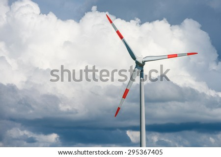 Close-up of wind turbine with cloudy sky - stock photo