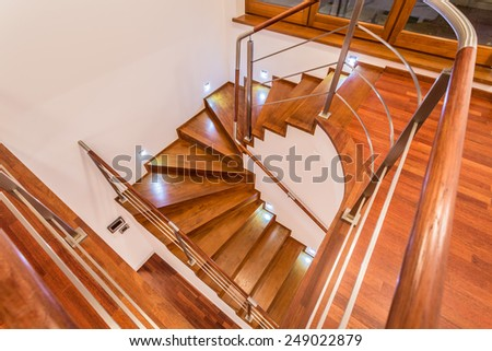 Close-up of winding wooden stairs in luxury mansion - stock photo