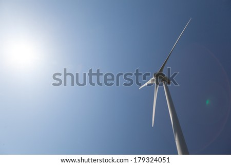 Close up of Windturbine with a clear blue sky and lensflare