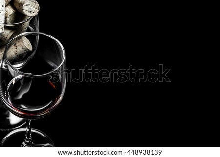 Close-up of wine glasses and corks on black background