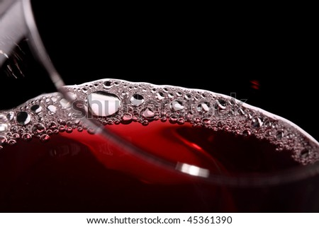 close up of wine in a glass isolated on black - stock photo