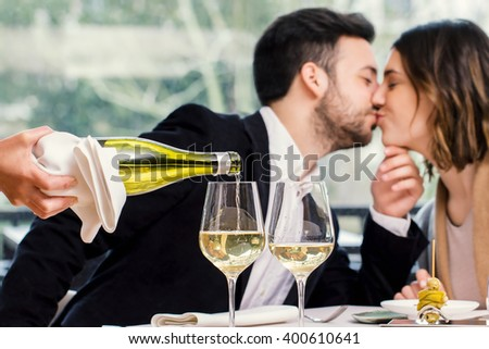 Close up of wine steward pouring white wine in glass with out of focus kissing couple in background. - stock photo