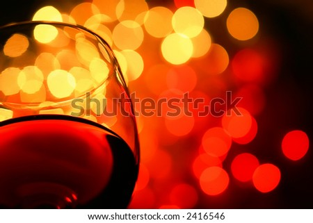 close-up of wineglass with copyspace and abstract lights background - stock photo