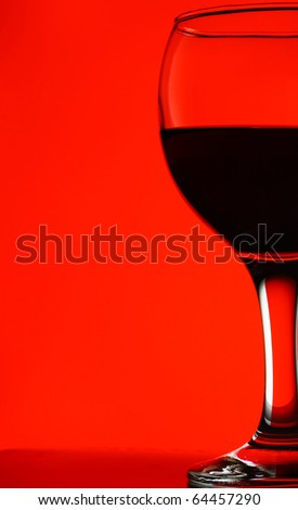 close-up of wineglass with red wine on red background