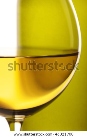 Close-up of wineglass with white wine and bottle in back light on white background. - stock photo