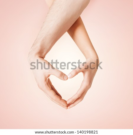 close up of woman and man hands showing heart shape - stock photo