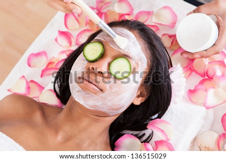 Close-up Of Woman Applying Facial Mask In Spa - stock photo