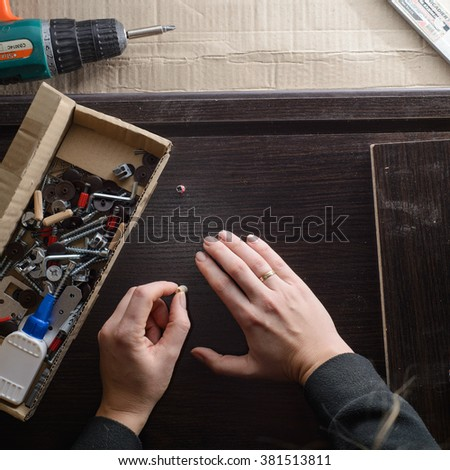 Close Up Of woman Assembling Furniture. top view. - stock photo