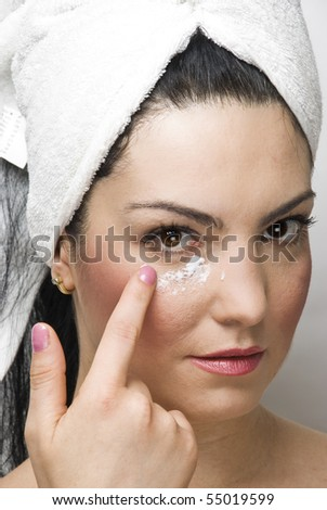 Close up of woman at dayspa applying cream of face