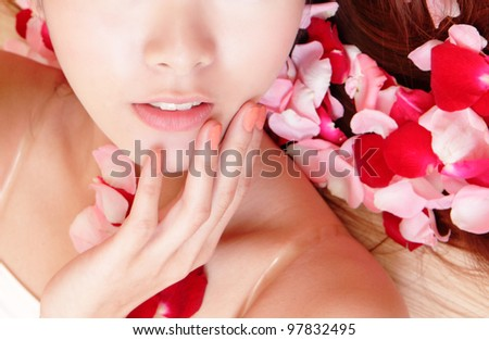 Close-up of woman beautiful lips with pink and red roses, model is a asian beauty - stock photo