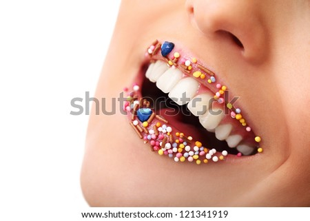 Close up of woman beautiful smile and lips with multicolored pearls - stock photo