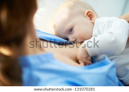 Close-up of woman breastfeeding her small son - stock photo