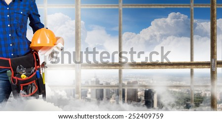 Close up of woman builder with hardhat in hands - stock photo