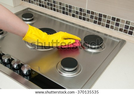 Close up of woman cleaning cooker at home kitchen - stock photo