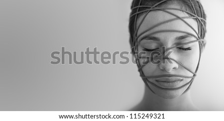 Close up of woman constrained with ropes. Black and white conceptual image. - stock photo