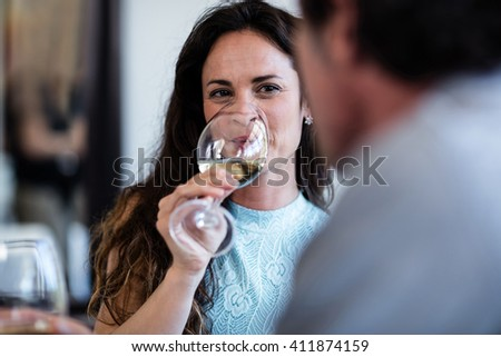 Close-up of woman drinking wine in a restaurant - stock photo