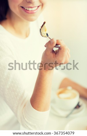 close up of woman eating cake at cafe or home - stock photo
